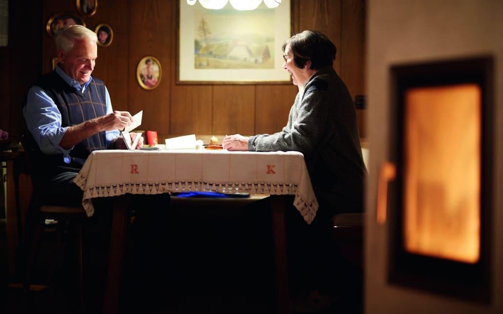 Foto von zwei Personen die neben einem Kachelofen sitzen