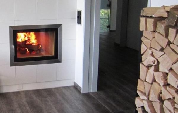 Foto eines Kachelofens von Hafnertec neben einem Holzstoß