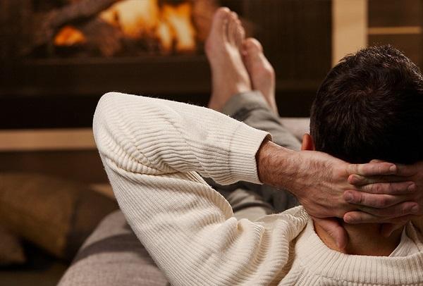 Foto einer Person, die auf einem Sofa vor einem Kachelofen von Hafnertec liegt