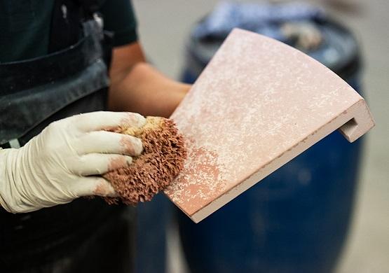 Foto einer Person, die eine Ofenkachel bemalt