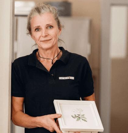 Foto einer Mitarbeiterin von Hafnertec, die eine bemalte Kachelofenfliese in der Hand hält