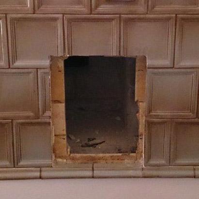 Foto des Einbauprozesses einer AFD Türe in einen älteren Kachelofen
