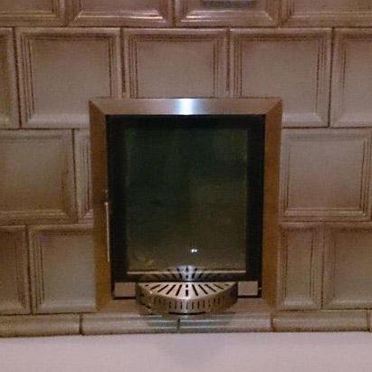 Foto einer AFD Türe, die in einem älteren Kachelofen eingebaut ist