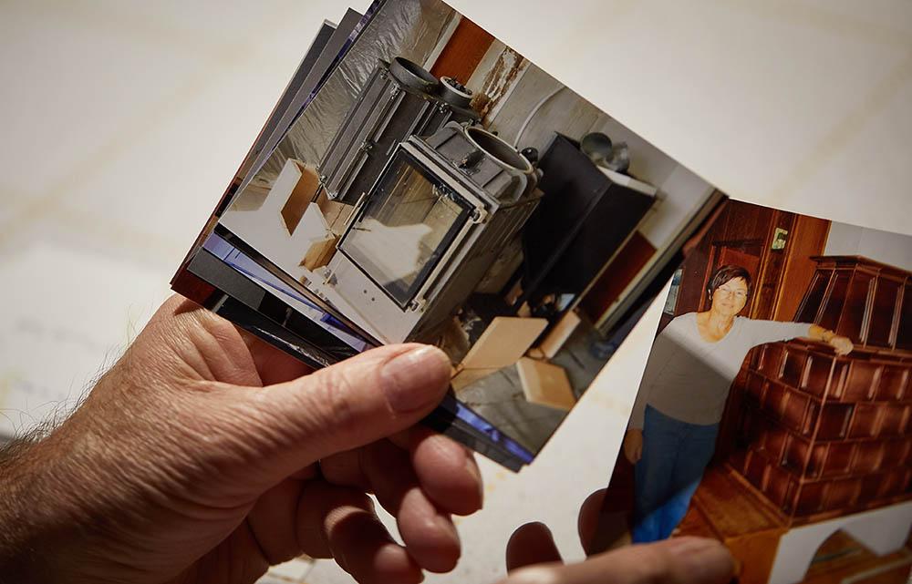 Foto von einer Person, die mehrere Fotos von einem älteren Kachelofen in der Hand hält
